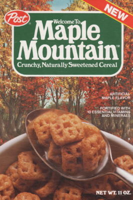 Front cover of Maple Mountain Cereal box featuring waffle shaped cereal in a bowl with spoon and maple trees in background