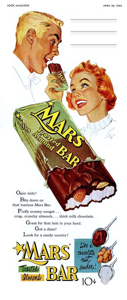 Vertical ad for Mars Bars from 1954. Ad shows heads of a man and woman sharing a candy bar, a large mars bar in middle, and ingredients on the bottom.