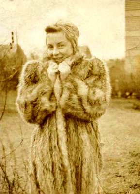 A portrait of illustrator Barbara Shermund in a fur coat, outside. Sepia tone, vintage photograph.
